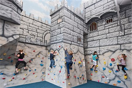 preteen girls stretching - Group of children playing and climbing at castle at indoor climbing centre Stock Photo - Premium Royalty-Free, Code: 649-07560191