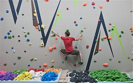 Route setter trying bouldering problem at indoor climbing wall Stock Photo - Premium Royalty-Free, Code: 649-07560193