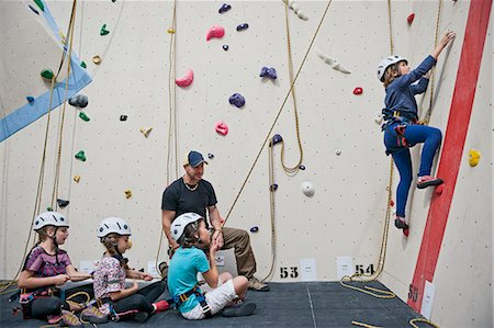 preteen girls stretching - Male instructor working with group of children on climbing wall Stock Photo - Premium Royalty-Free, Code: 649-07560202