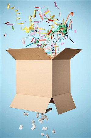 exploding - Studio shot of cardboard box with streamers exploding out Stock Photo - Premium Royalty-Free, Code: 649-07560260