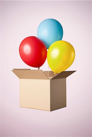 ebusiness - Studio shot of cardboard box with balloons coming out Stock Photo - Premium Royalty-Free, Code: 649-07560261