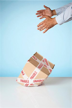 ebusiness - Studio shot of hands dropping cardboard box marked fragile Stock Photo - Premium Royalty-Free, Code: 649-07560263