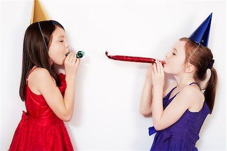 Portrait of two girls blowing party blowers Stock Photo - Premium Royalty-Free, Code: 649-07560306