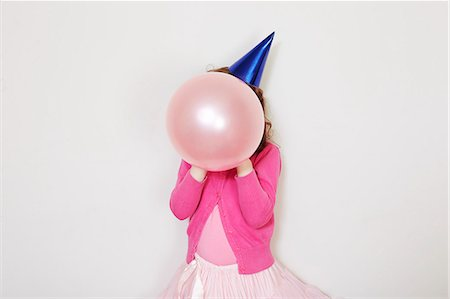 Girl holding pink balloon in front of face Stock Photo - Premium Royalty-Free, Code: 649-07560318