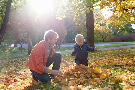 Father and son playing with autumn leaves Stock Photo - Premium Royalty-Free, Code: 649-07560333