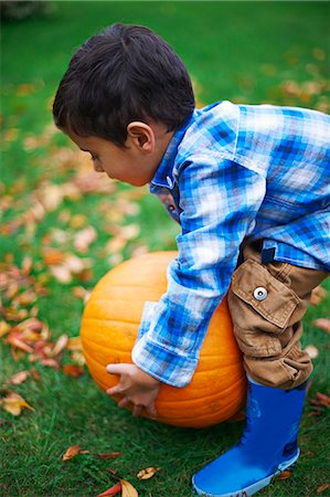 Male toddler in the garden picking up pumpkin Stock Photo - Premium Royalty-Free, Code: 649-07560360