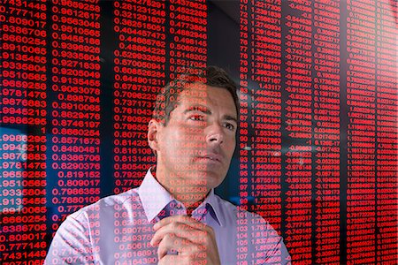 Businessman working with red figures seen through screen Stock Photo - Premium Royalty-Free, Code: 649-07560475