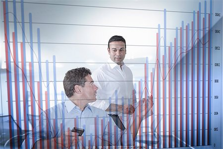 east indian (male) - Businessmen discussing bar chart seen through screen Stock Photo - Premium Royalty-Free, Code: 649-07560477