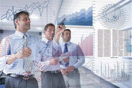 Businessmen discussing graphs and charts seen through screen Stock Photo - Premium Royalty-Free, Code: 649-07560478