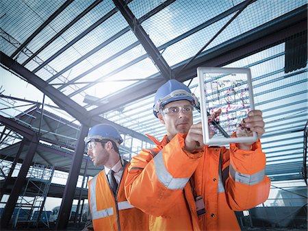 Builders working on plan details using digital tablet Stock Photo - Premium Royalty-Free, Code: 649-07560470