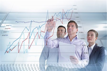 Business colleagues discussing graphs and charts seen on interactive display Stock Photo - Premium Royalty-Free, Code: 649-07560471
