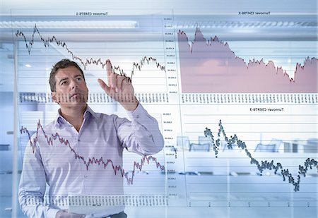 displaying - Businessman inspects graphs seen through interactive display Stock Photo - Premium Royalty-Free, Code: 649-07560472