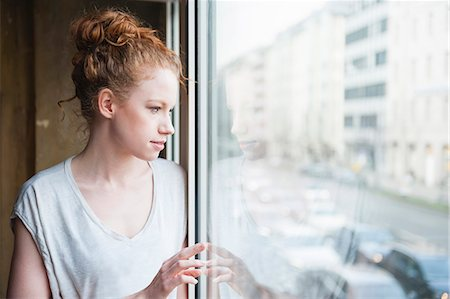 Young woman looking out of window at street Stock Photo - Premium Royalty-Free, Code: 649-07560488