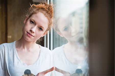 femininity - Portrait of young woman leaning against window Stock Photo - Premium Royalty-Free, Code: 649-07560489