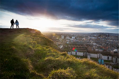 A young couple hold hands in front of the view of the City of Edinburgh from Salisbury Crags Stockbilder - Premium RF Lizenzfrei, Bildnummer: 649-07560512