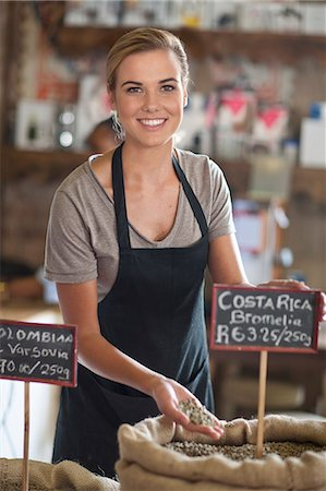 Portrait of young female waitress holding coffee beans in cafe Stock Photo - Premium Royalty-Free, Code: 649-07585064