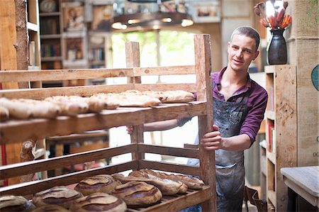 Portrait of young male baker with shelves of fresh bread Stock Photo - Premium Royalty-Free, Code: 649-07585068