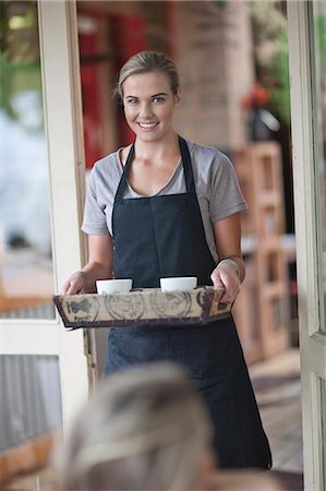 Young female waitress carrying tray of coffee cups in cafe Stock Photo - Premium Royalty-Free, Code: 649-07585061