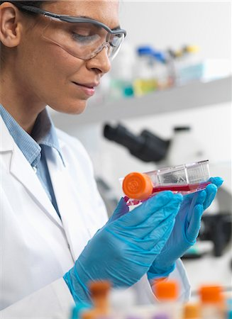 science & technology - Female cell biologist holding a flask containing stem cells, cultivated in red growth medium, to investigate disease Stock Photo - Premium Royalty-Free, Code: 649-07585091