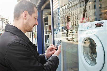 retail store - Mid adult man checking out washing machine in shop using smartphone Stock Photo - Premium Royalty-Free, Code: 649-07585106