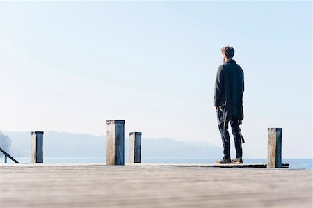 european - Mid adult man standing on pier, rear view Stock Photo - Premium Royalty-Free, Code: 649-07585150