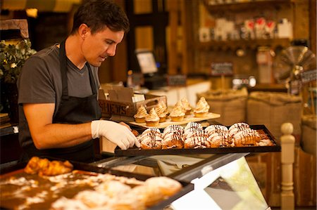 Mature man with tray of fresh pastries Stock Photo - Premium Royalty-Free, Code: 649-07585191