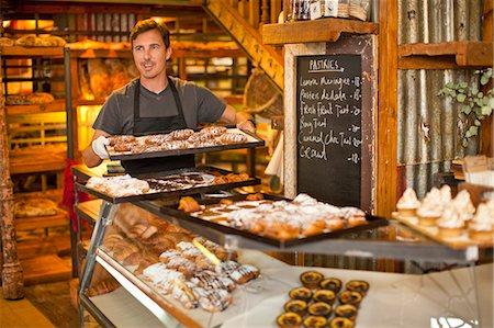 Mature man holding tray of fresh pastries Stock Photo - Premium Royalty-Free, Code: 649-07585192
