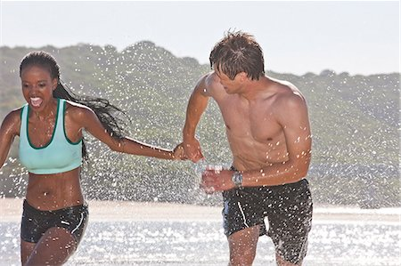 partnership - Young couple holding hands running through sea Stock Photo - Premium Royalty-Free, Code: 649-07585205