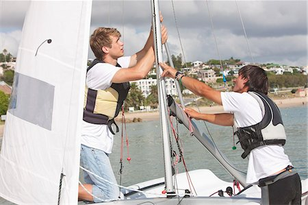 sports and sailing - Two young men hauling up sail on boat Stock Photo - Premium Royalty-Free, Code: 649-07585247
