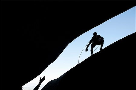 reaching - Silhouette of young male climbers reaching out for each other on rock Stock Photo - Premium Royalty-Free, Code: 649-07585243