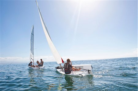 friendship - Young adult friends racing each other in sailboats Stock Photo - Premium Royalty-Free, Code: 649-07585250