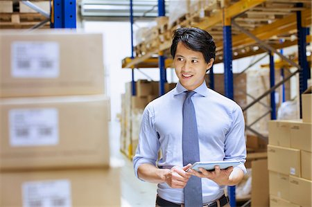 piles of work - Mid adult male manager using digital tablet in distribution warehouse Stock Photo - Premium Royalty-Free, Code: 649-07585276
