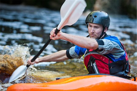 Close up of mid adult man kayaking on river rapids Stock Photo - Premium Royalty-Free, Code: 649-07585293