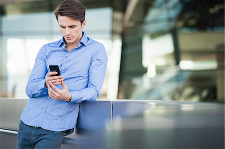 Mid adult man leaning against wall reading texts on smartphone Stock Photo - Premium Royalty-Free, Code: 649-07585395