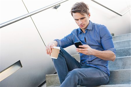 device - Mid adult man reading smartphone messages on city steps Stock Photo - Premium Royalty-Free, Code: 649-07585393