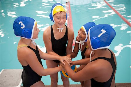 Four schoolgirl water polo players holding hands poolside Stock Photo - Premium Royalty-Free, Code: 649-07585408