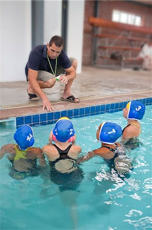 Four schoolgirl water polo players listening to teacher poolside Stock Photo - Premium Royalty-Free, Code: 649-07585410