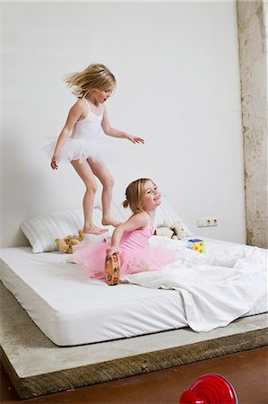 dress up girl - Two young sisters dressed as ballet dancers playing on bed Stock Photo - Premium Royalty-Free, Code: 649-07585444
