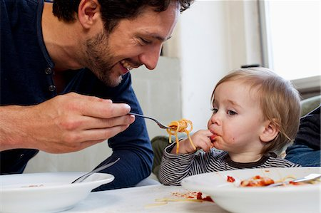 Father feeding one year old daughter spaghetti Stock Photo - Premium Royalty-Free, Code: 649-07585440