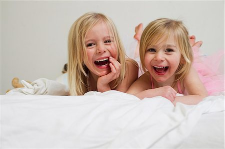 dress up girl - Portrait of two young sisters lying on front in bed Stock Photo - Premium Royalty-Free, Code: 649-07585454