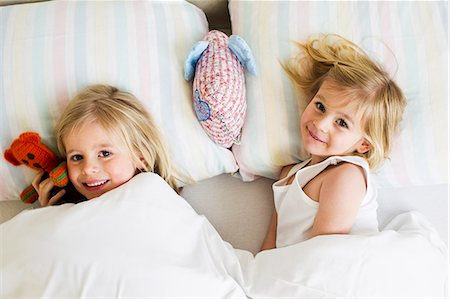 Portrait of two young sisters lying side by side in bed Stock Photo - Premium Royalty-Free, Code: 649-07585465
