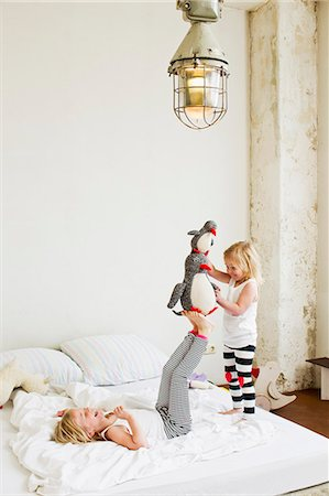 Young sisters playing with soft toy on the bed Stock Photo - Premium Royalty-Free, Code: 649-07585468