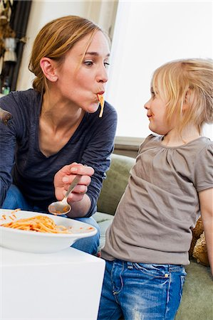 sucking - Mid adult mother eating spaghetti with her daughter Stock Photo - Premium Royalty-Free, Code: 649-07585474