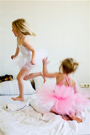 dress up girl - Sisters dressed as ballet dancers running on bed Stock Photo - Premium Royalty-Free, Code: 649-07585477
