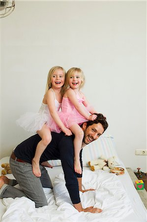 Portrait of mid adult father giving two young daughters a piggy back Stock Photo - Premium Royalty-Free, Code: 649-07585478