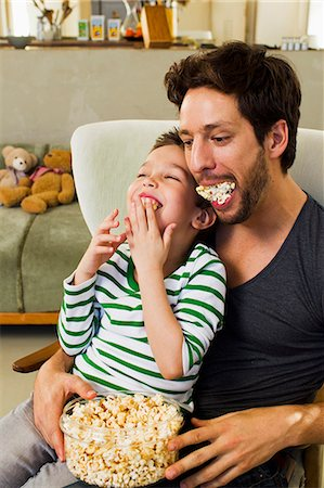 father son bath - Father and young son with mouthfuls of popcorn Stock Photo - Premium Royalty-Free, Code: 649-07585485