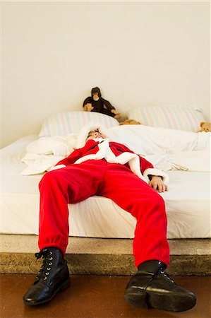 Young boy dressed up as santa claus lying on bed Stock Photo - Premium Royalty-Free, Code: 649-07585486