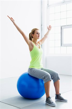 Young woman sitting on exercise ball, arms raised Stock Photo - Premium Royalty-Free, Code: 649-07585499