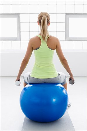 fit people - Young woman sitting on exercise ball, rear view, with weights Stock Photo - Premium Royalty-Free, Code: 649-07585504
