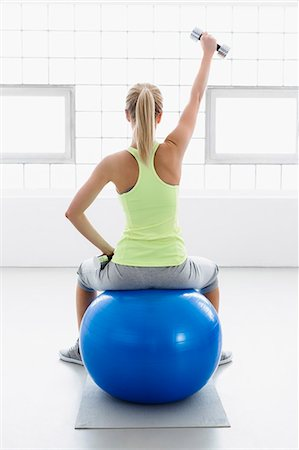 Young woman sitting on exercise ball, rear view, lifting weights Stock Photo - Premium Royalty-Free, Code: 649-07585505